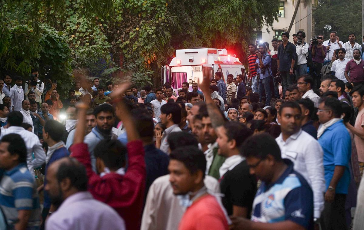 People look on as firefighters conduct rescue after a major fire broke out at ESIC Kamgar Hospital, in Mumbai.