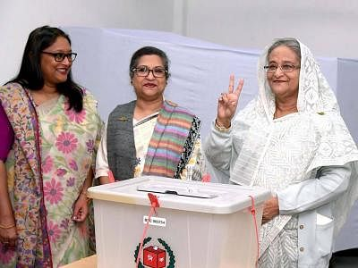 DHAKA, Dec. 30, 2018 (Xinhua) -- Bangladesh Prime Minister Sheikh Hasina(R) flashes a victory sign after casting her vote at a polling station in Dhaka, capital of Bangladesh, on Dec. 30, 2018. Nationwide voting opened Sunday morning in Bangladesh