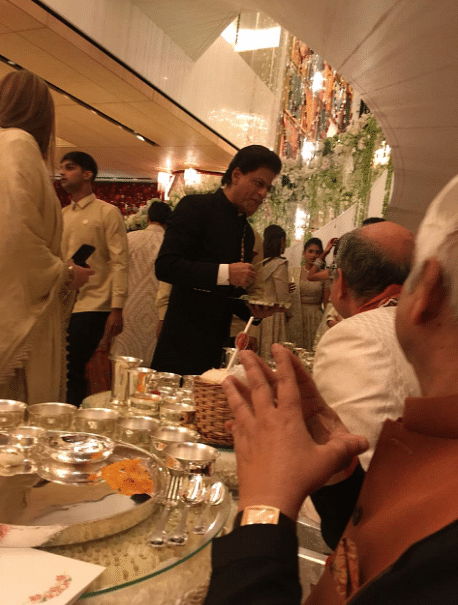 Shah Rukh Khan seen here serving food to guests at the wedding.