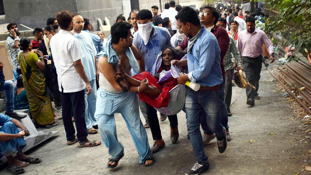 People carry the injured during a rescue operation after a major fire broke out at ESIC Kamgar Hospital, in Mumbai, on 17 December.