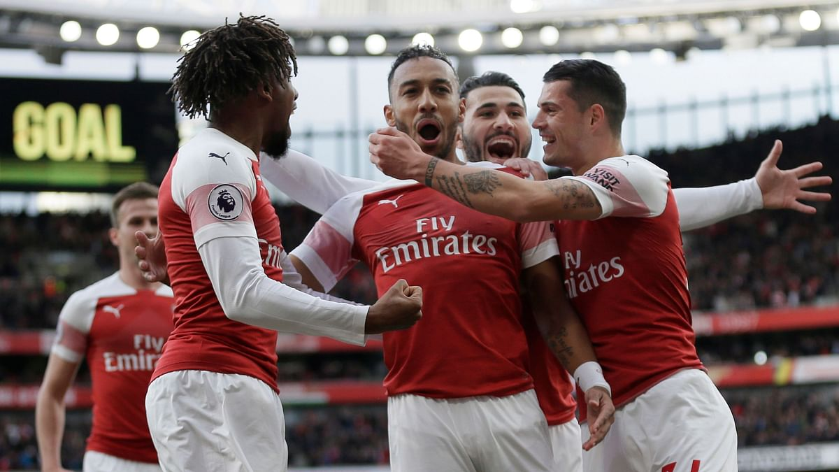 Arsenal's Pierre-Emerick Aubameyang, center, celebrates with his teammates after scoring his side's opening goal from a penalty spot during the English Premier League.