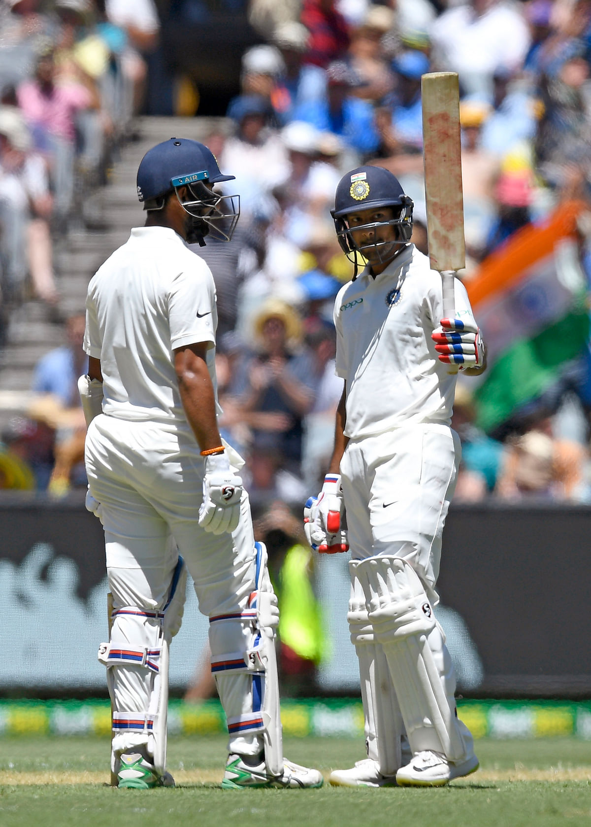 India's Mayank Agarwal, right celebrates with team mate, left Cheteshwar Pujara after scoring a half century on day one of the third cricket test between India and Australia in Melbourne, Australia, Wednesday, Dec. 26, 2018.