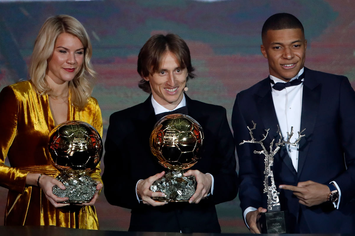 Real Madrid's Luka Modric, with the Ballon d'Or, center poses with Olympique Lyonnais' Ada Hegerberg with the Women's Ballon d'Or, left, and Paris St Germain's Kylian Mbappe with the Kopa Trophy, right, during the Golden Ball award ceremony at the Grand Palais in Paris.