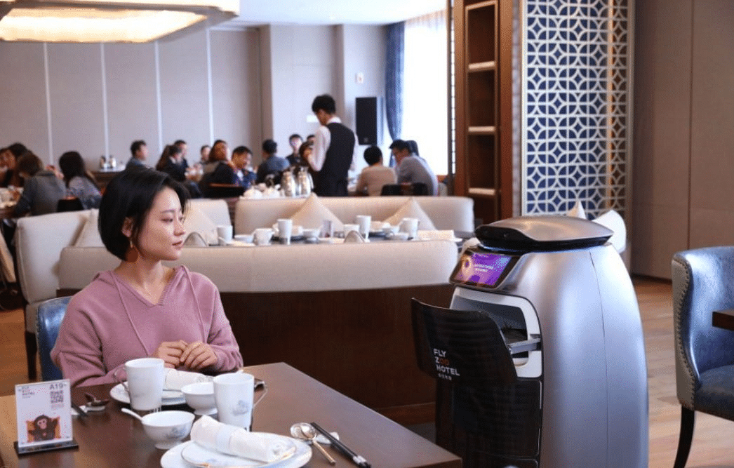 The Flyzoo robot waiter serves food to a customer.