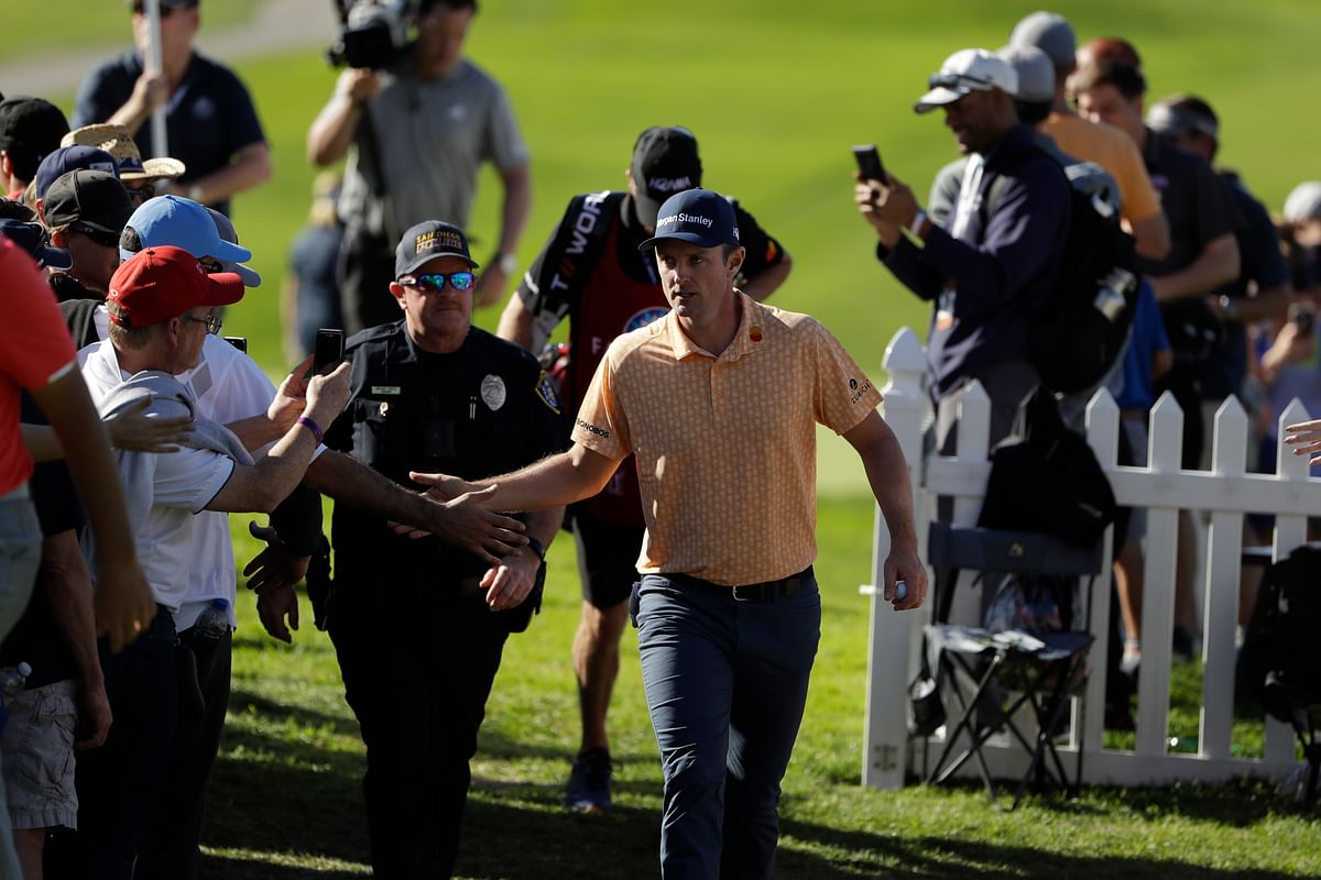 Justin Rose, of England, greets fans as he makes his way to the 14th hole of the South Course at Torrey Pines Golf Course during the final round of the Farmers Insurance golf tournament Sunday, Jan. 27, 2019, in San Diego.