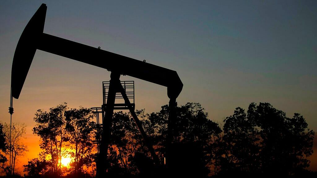 The sun sets behind an oil well in a field near El Tigre, a town within Venezuela's Hugo Chavez oil belt, formally known as the Orinoco Belt.