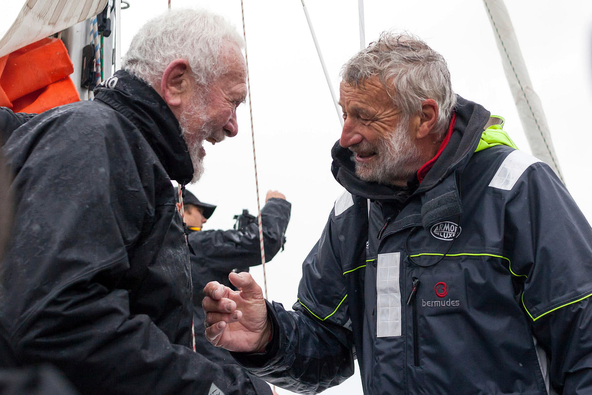 French sailor Jean-Luc Van Den Heede, 73, right, aboard his Rustler 36, Matmut, is congratulated by legendary sailor Sir Robin Knox-Johnston of Britain, after winning the Golden Globe Race, a single-handed round the world yacht race, after 212 days alone at sea, in Les Sables-d'Olonne harbor, western France, Tuesday, Jan. 29, 2019.