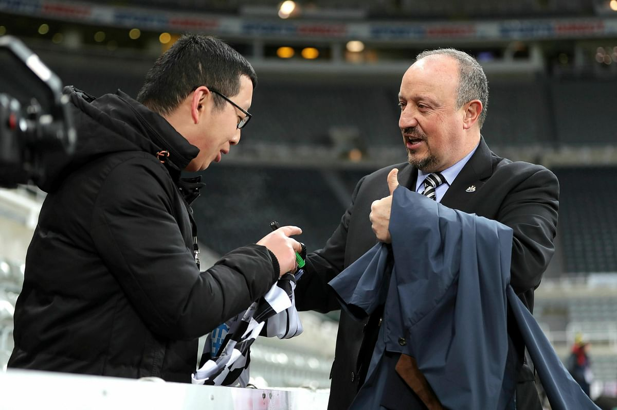 Newcastle United manager Rafael Benitez, right, signs an autograph as he arrives for the English Premier League soccer match against Newcastle, at St James' Park in Newcastle, Tuesday Jan. 29, 2019.