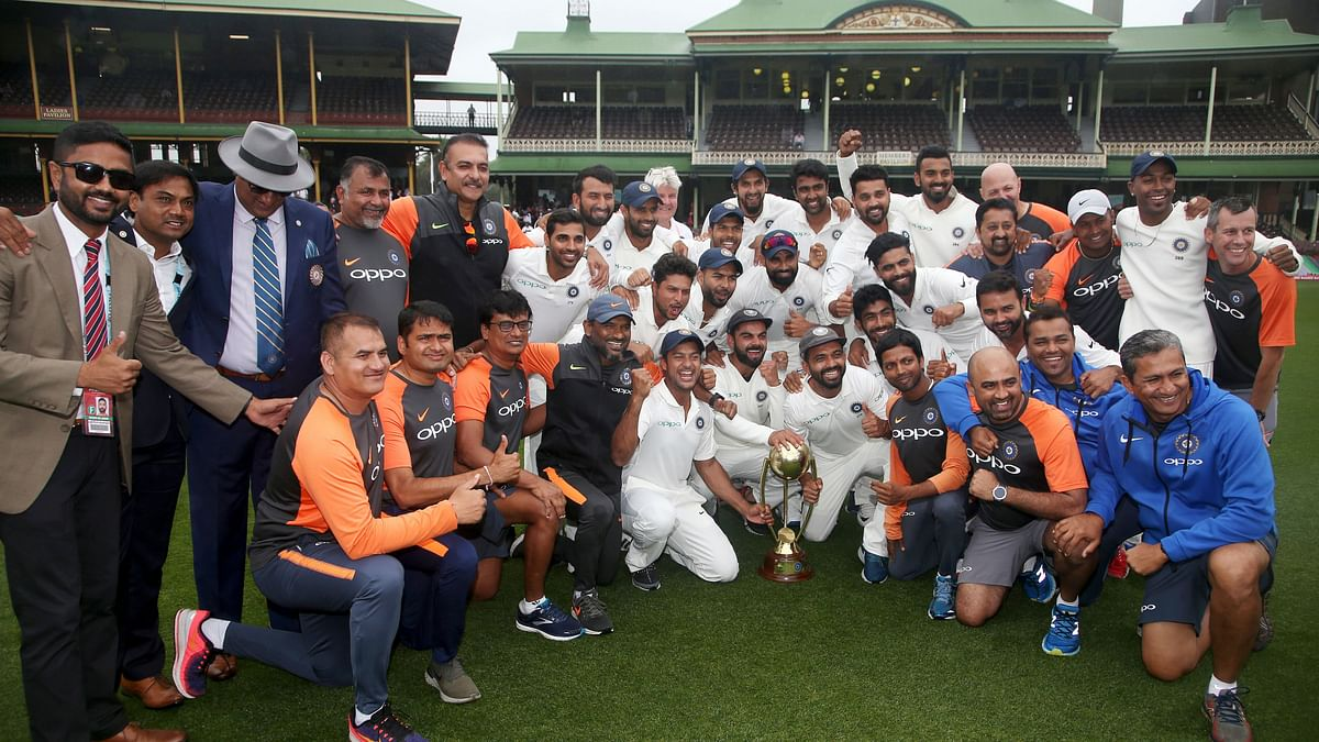 The Indian squad and support staff pose with the Border-Gavaskar Trophy after securing India's maiden Test series win in Australia.
