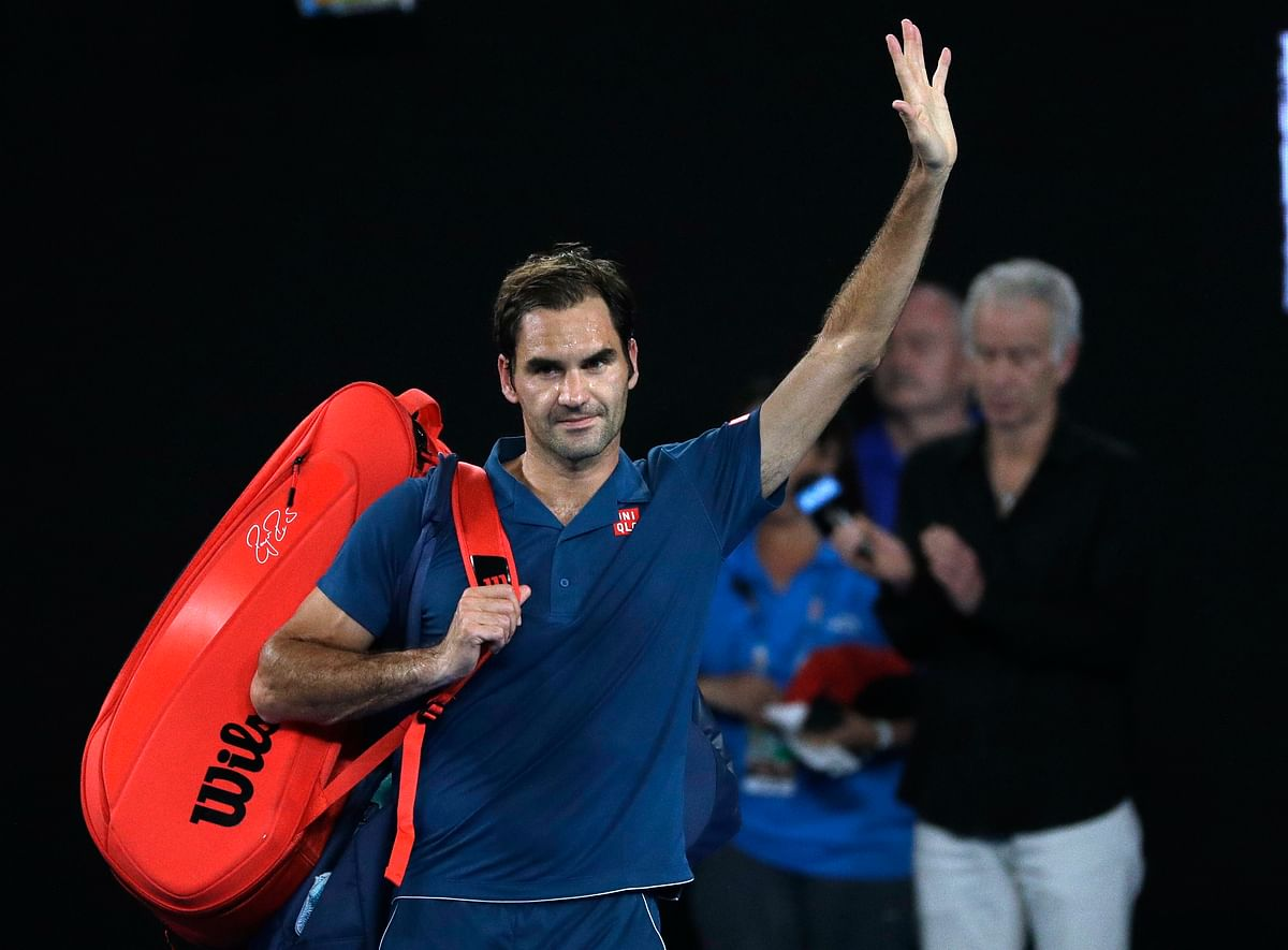 Switzerland's Roger Federer waves as he leaves Rod Laver Arena after losing his fourth round match against Greece's Stefanos Tsitsipas at the Australian Open.