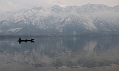 Srinagar: A boatman seen rowing his boat through serene waters of the Dal Lake with snow-covered mountains in the backdrop on a chilly winter morning in Srinagar, on Jan 28, 2019. (Photo: IANS)