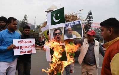 Patna: People burn pictures of Pakistan Prime Minister Imran Khan, Jamaat-ud-Dawa chief Hafiz Saeed and Pakistan flag as they protest against suicide attack on a CRPF bus in Jammu and Kashmir