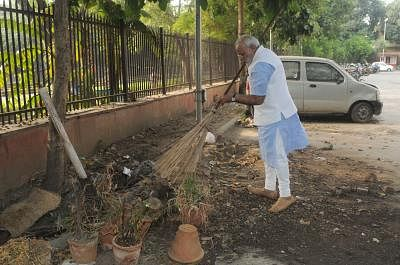 Prime Minister Narendra Modi cleans the premises of Mandir Marg Police Station during his surprise visit, in New Delhi, on Oct. 2, 2014. (Photo: IANS/PIB)