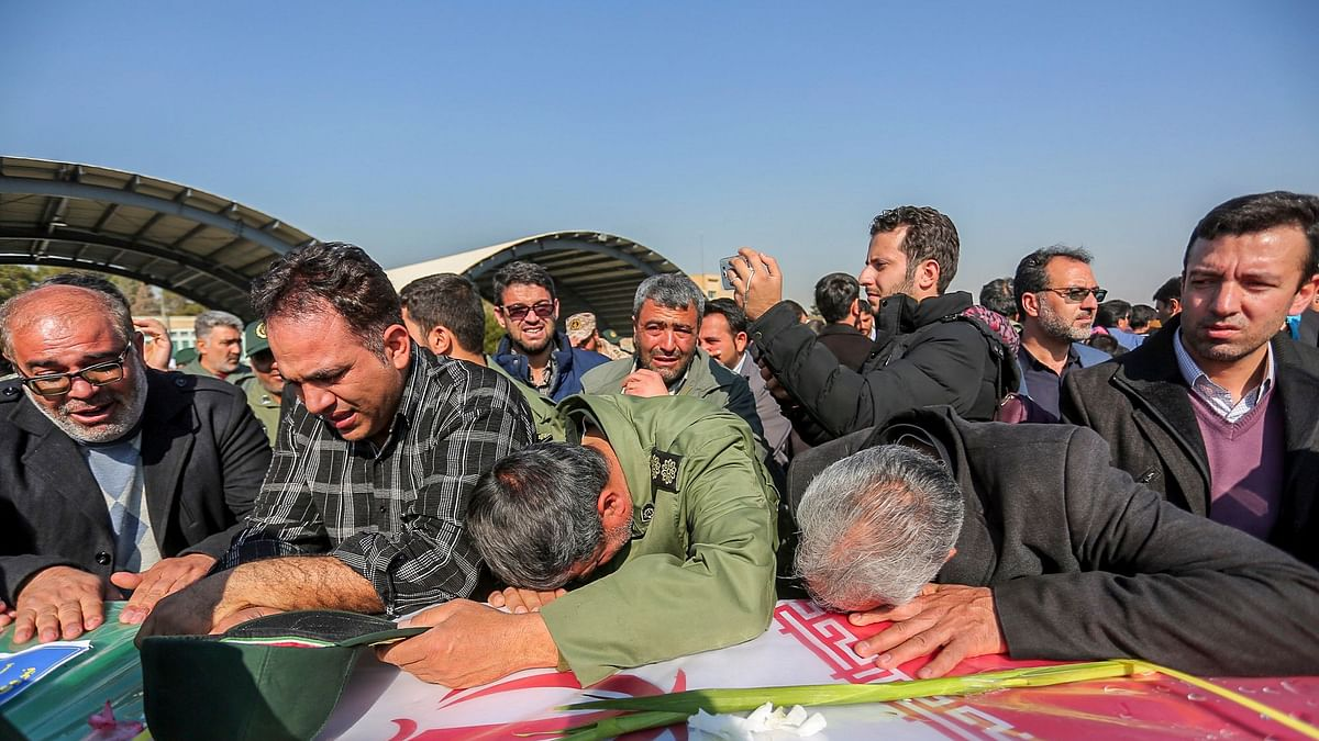 In this photo provided by Tasnim News Agency, mourners weep over a flag-draped coffin of a member of Iran's Revolutionary Guard who was killed in a suicide car bombing in Iran.