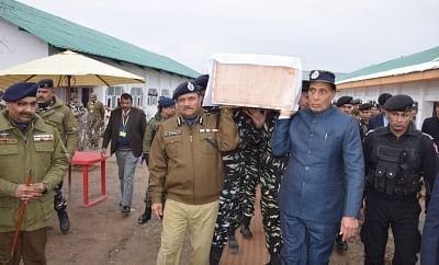 Budgam: Union Home Minister Rajnath Singh lifts the coffin of one of the one of the 45 CRPF personnel killed in a suicide attack by militants in Jammu and Kashmir