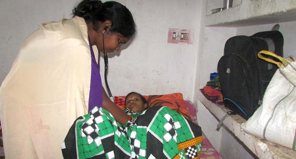 Maa Gruha coordinator Pushpita Sahu checks a pregnant woman staying at one of the maternity waiting homes .