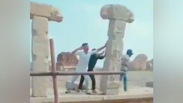 Men vandalising a pillar in Hampi