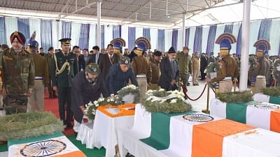 Srinagar: Union Home Minister Rajnath Singh lays wreath on the coffins of martyred CRPF soldiers, at the Regional Training Centre, in Srinagar on Feb 15, 2019. Also seen Jammu and Kashmir Governor Satya Pal Malik, Union Home Secretary Rajiv Gauba, CRPF Director General Rajeev Rai Bhatnagar and GoC-in-C, Army