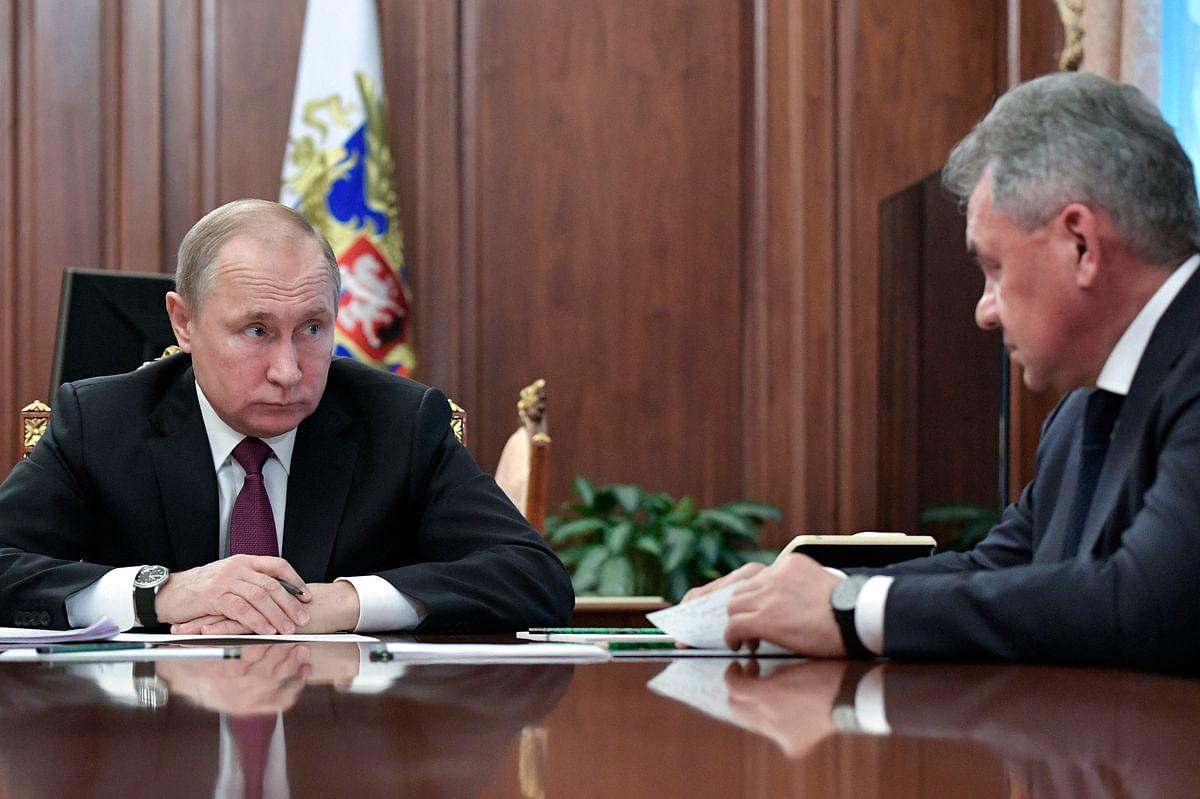 Russian President Vladimir Putin, left, speaks to Defense Minister Sergei Shoigu.