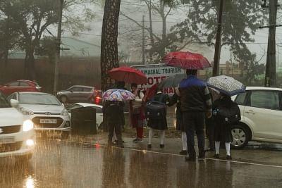 Dharamshala: People shield themselves with umbrellas during rains in Dharamshala, Himachal Pradesh on Feb 7, 2019. (Photo: IANS)