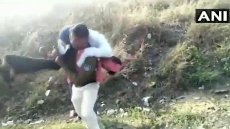 A man fell from a moving train and a constable carries him on his shoulders to safety.