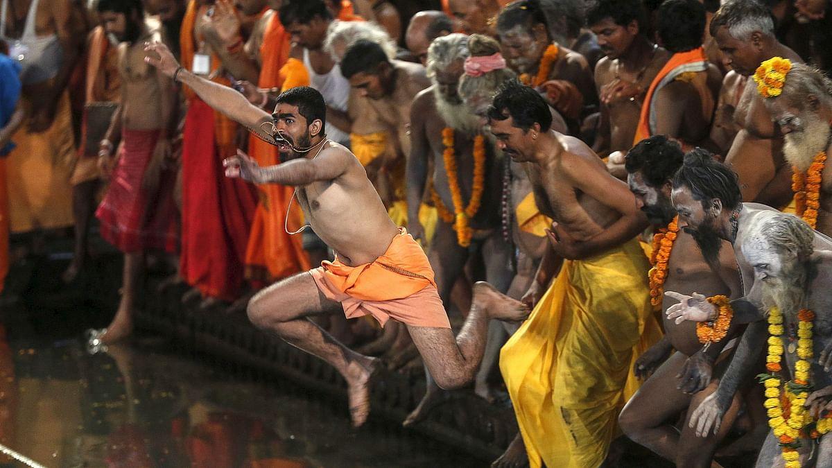 Sadhus jump in a holy pond during the <i>shahi snan</i> at the Kumbh Mela.