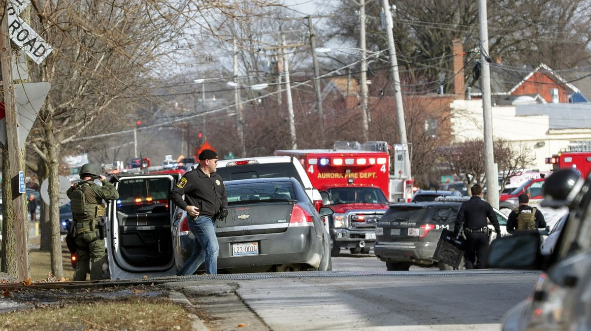 Law enforcement personnel gather near the scene of a shooting at an industrial park in Aurora.