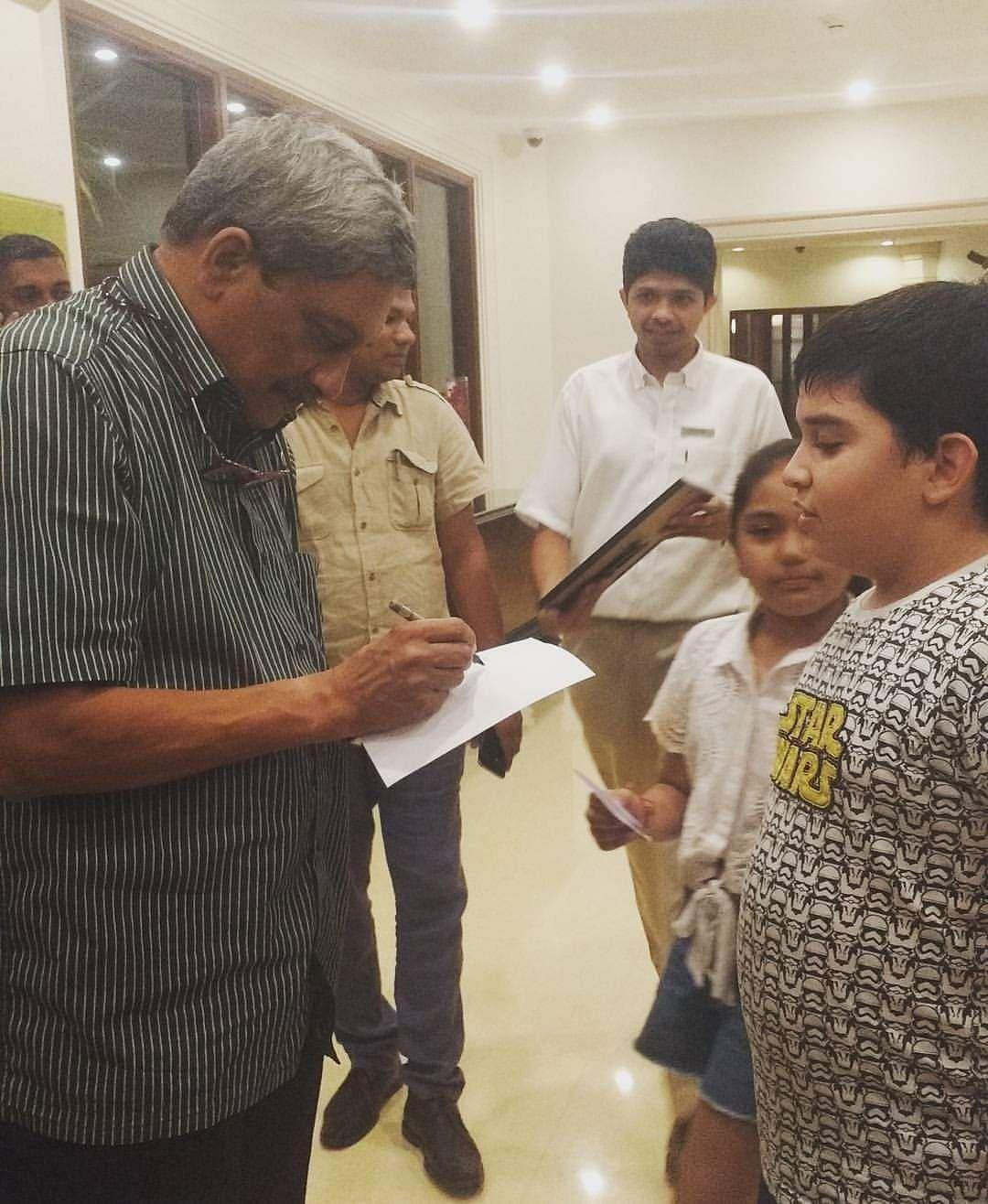 Manohar Parrikar signs an autograph for a kid.