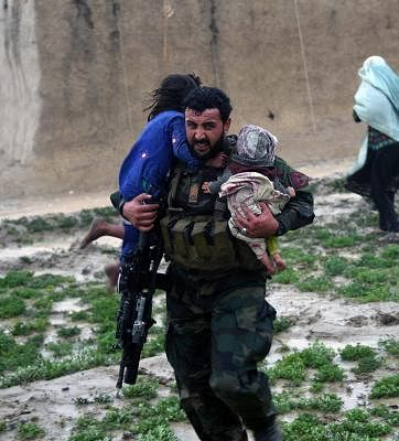 KANDAHAR, March 3, 2019 (Xinhua) -- An Afghan security force member rescues children during an evacuation operation after a flood in Kandahar province, Afghanistan, March 2, 2019 . At least 20 people were killed and many others went missing after flash floods hit Afghanistan
