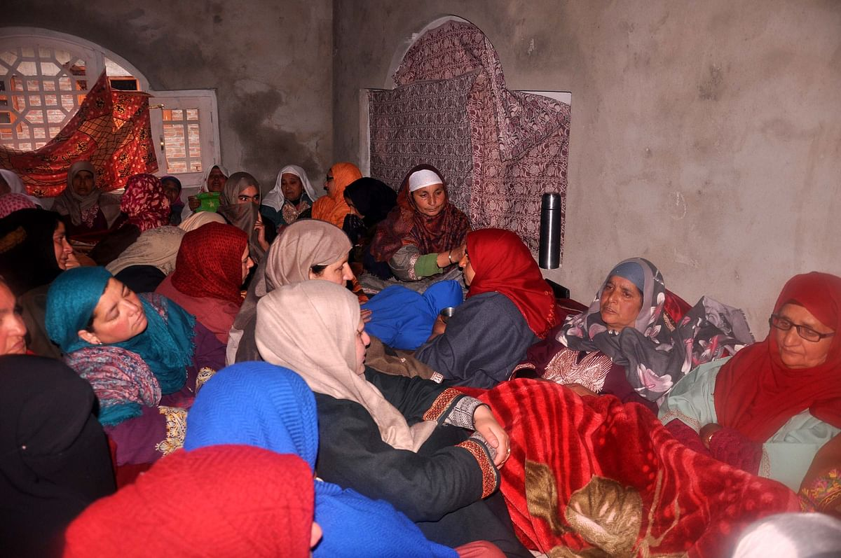 Neighbours and relatives of Rizwan, consoling his mother at his residence in Awantipora.
