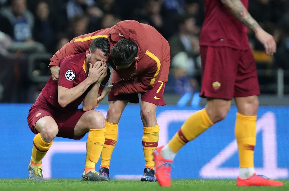 Roma midfielder Lorenzo Pellegrini comforts midfielder Alessandro Florenzi, left, at the end of the Champions League round of 16, 2nd leg, soccer match.