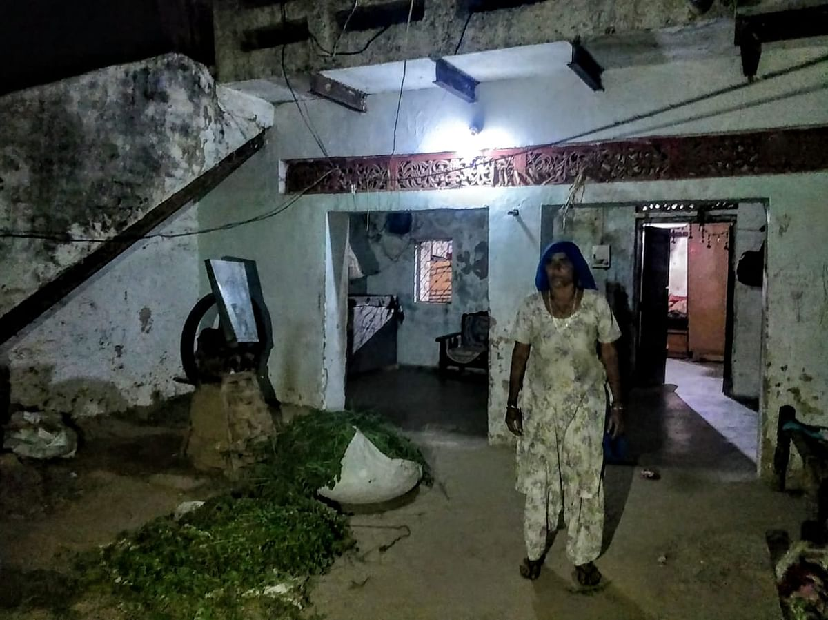 Mahesh's mother stands inside their home in Naya Gaon. She takes up any work she gets to help feed her family. Her husband died about seven years ago.