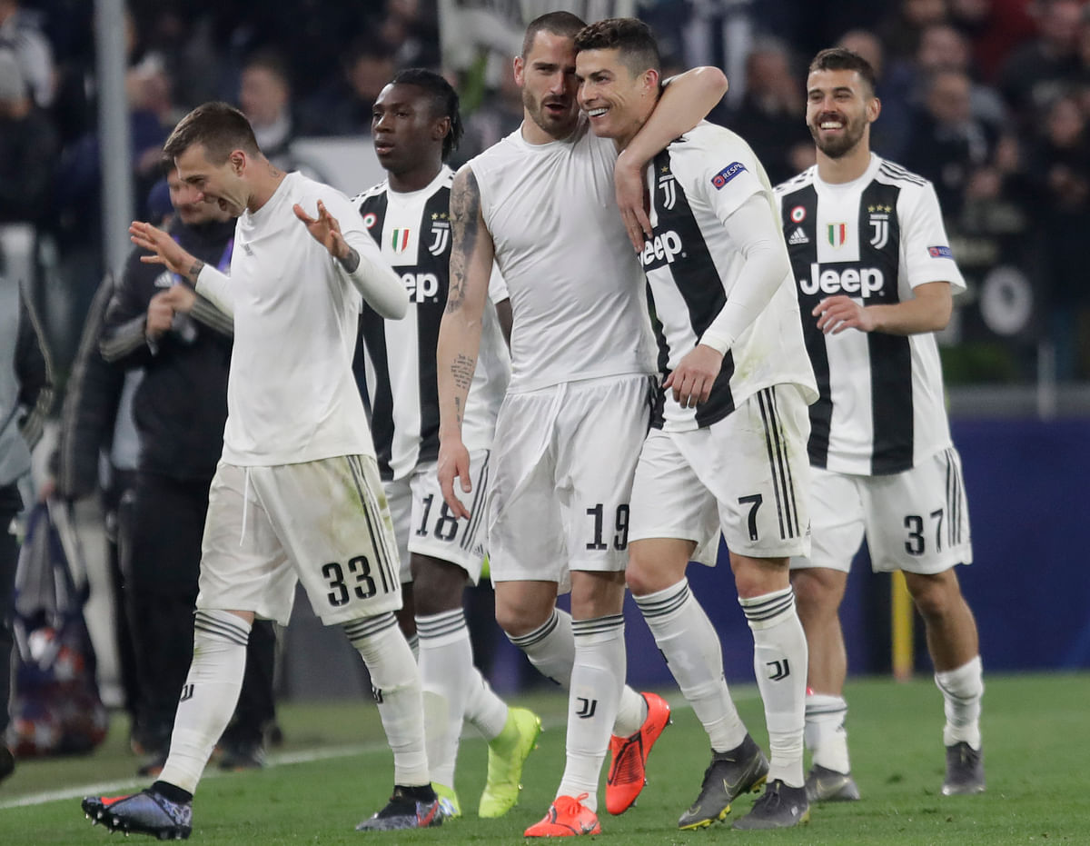 Juventus' Leonardo Bonucci, centre left and Cristiano Ronaldo hug at the end of the Champions League round of 16, 2nd leg, soccer match.