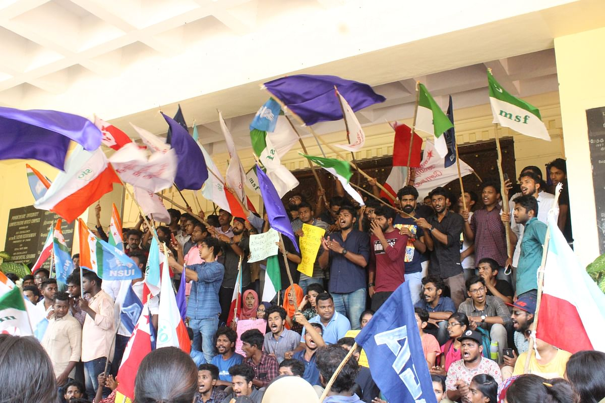Students wave flags outside the admin block.