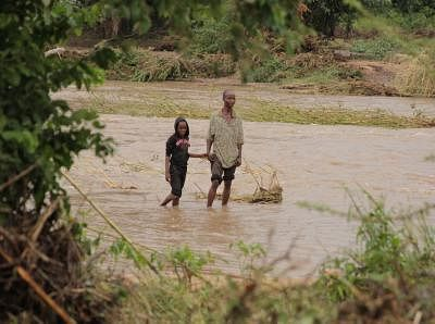 CHIMANIMANI (ZIMBABWE), March 17, 2019 (Xinhua) -- People walk through a flooded river in Chimanimani, Manicaland Province, Zimbabwe, March 17, 2019. At least 31 people have been confirmed dead while dozens of others are still missing as tropical cyclone Idai wreaks havoc in southeastern Zimbabwe, the government said Saturday evening. (Xinhua/Shaun Jusa/IANS)