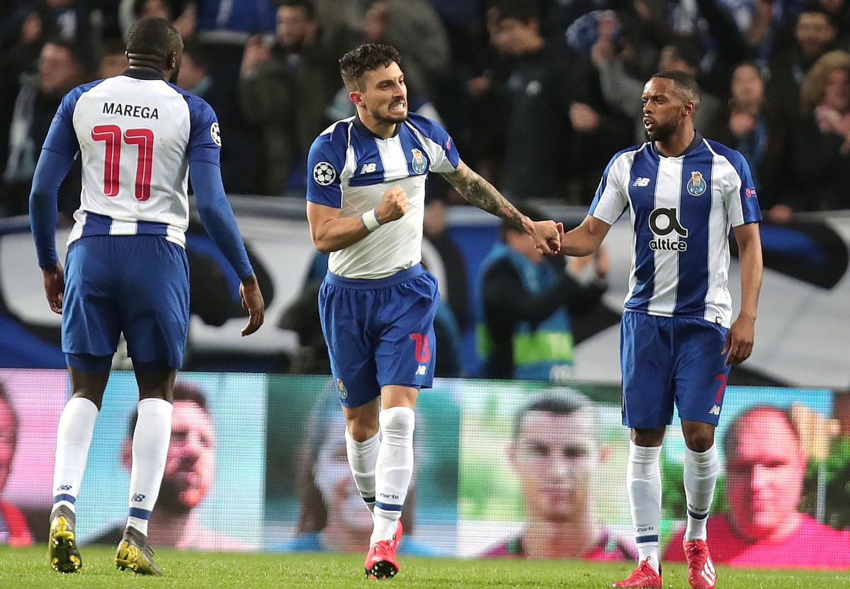 Porto defender Alex Telles, center, celebrates after scoring his side's third goal during the Champions League round of 16, 2nd leg, soccer match.