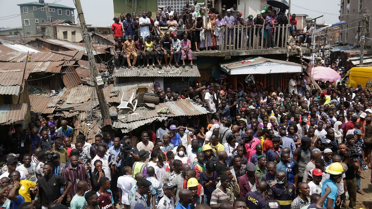People gather at the scene of a collapsed building in Lagos, Nigeria, Wednesday, 13 March 2019. Rescue efforts are underway in Nigeria after a three-storey school building collapsed while classes were in session, with some scores of children thought to be inside at the time.