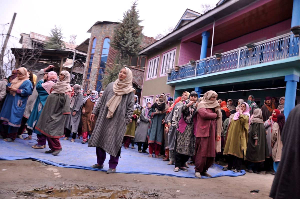 Neighbours gather outside Rizwan's house.