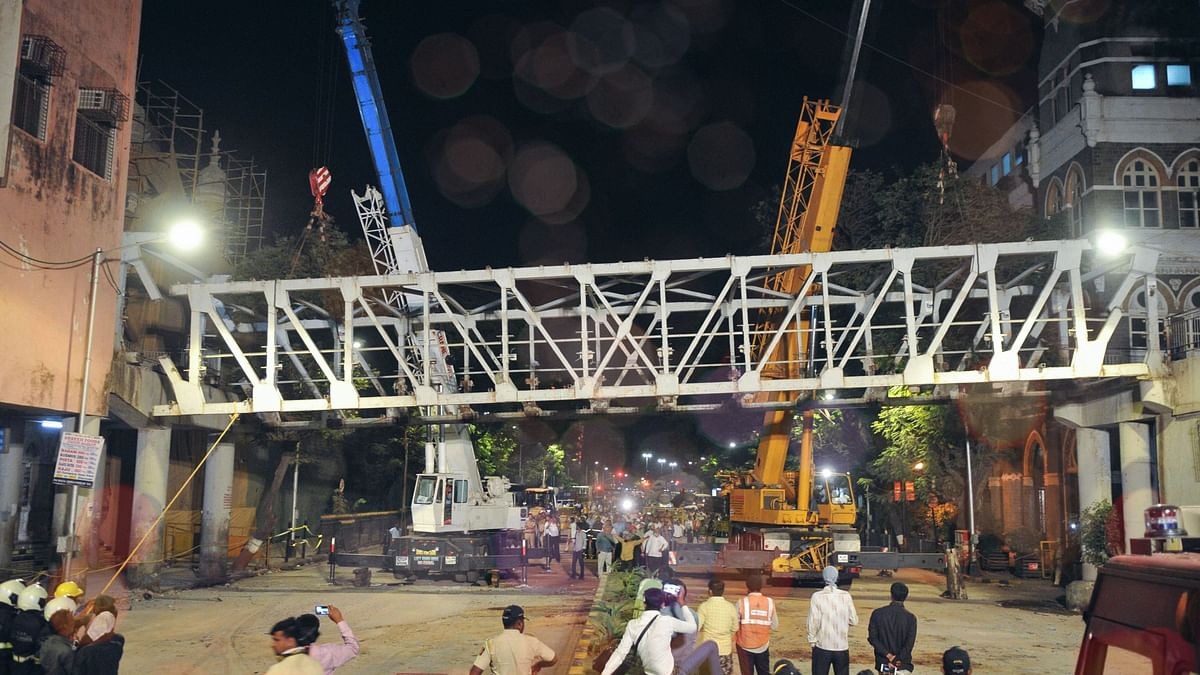 In this picture from 15 March, 2019, civic authorities are seen dismantling the bridge connecting the CST station and the are ear the TOI building, after it collapsed 14 March.