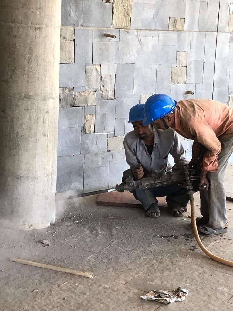 Workers drill holes into the pillar to plant the dynamites.