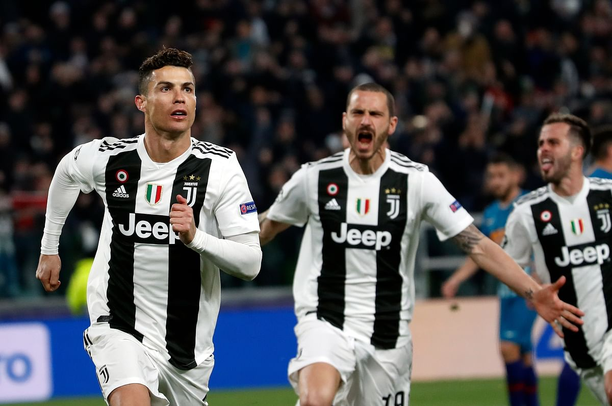 Juventus' Cristiano Ronaldo, left, celebrates after scoring his side's third goal during the Champions League round of 16, 2nd leg, soccer match.