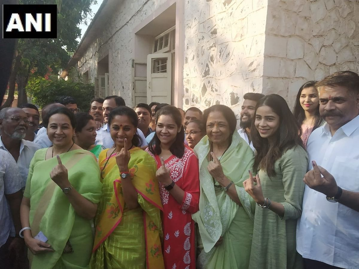 Nationalist Congress Party's Supriya Sule along with her family casts her vote a polling station in Baramati.