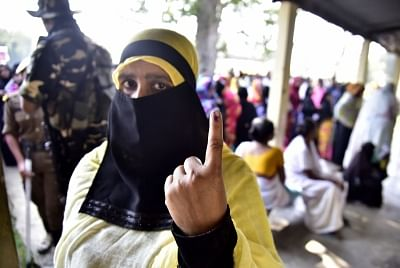 A Muslim woman shows her inked finger after casting vote.