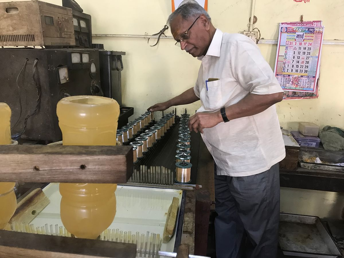 Shyam Sundar Jaiswal operating his machine that coats the silver thread with gold