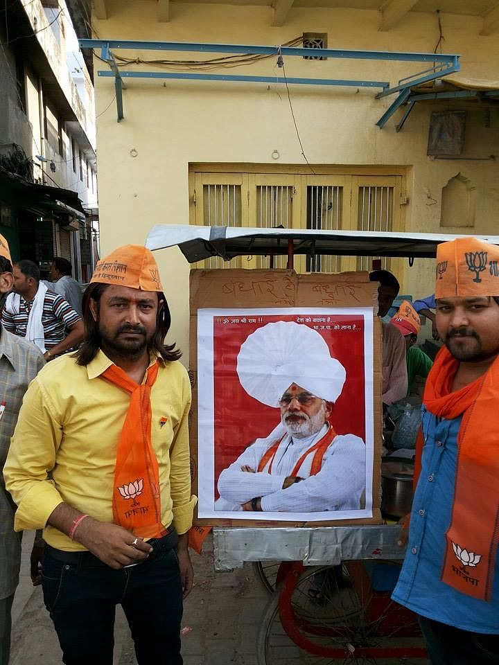 Vinay Kumar Shadeja (L) poses with a Modi poster in 2014, when he actively campaigned for the BJP in Varanasi.