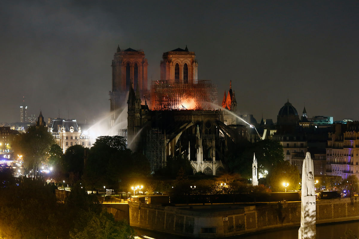Firefighters tackle the blaze as flames and smoke rise from Notre Dame cathedral as it burns in Paris, Monday, 15 April, 2019.