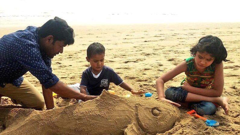 Sand artist Sudarsan Pattnaik with his children at Puri sea beach in Odisha.