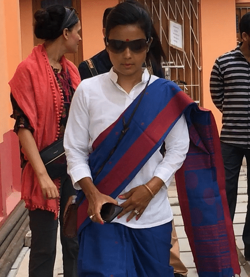 Mahua emerges in a red and blue Shantipuri saree, paired with a crisp, white t-shirt.