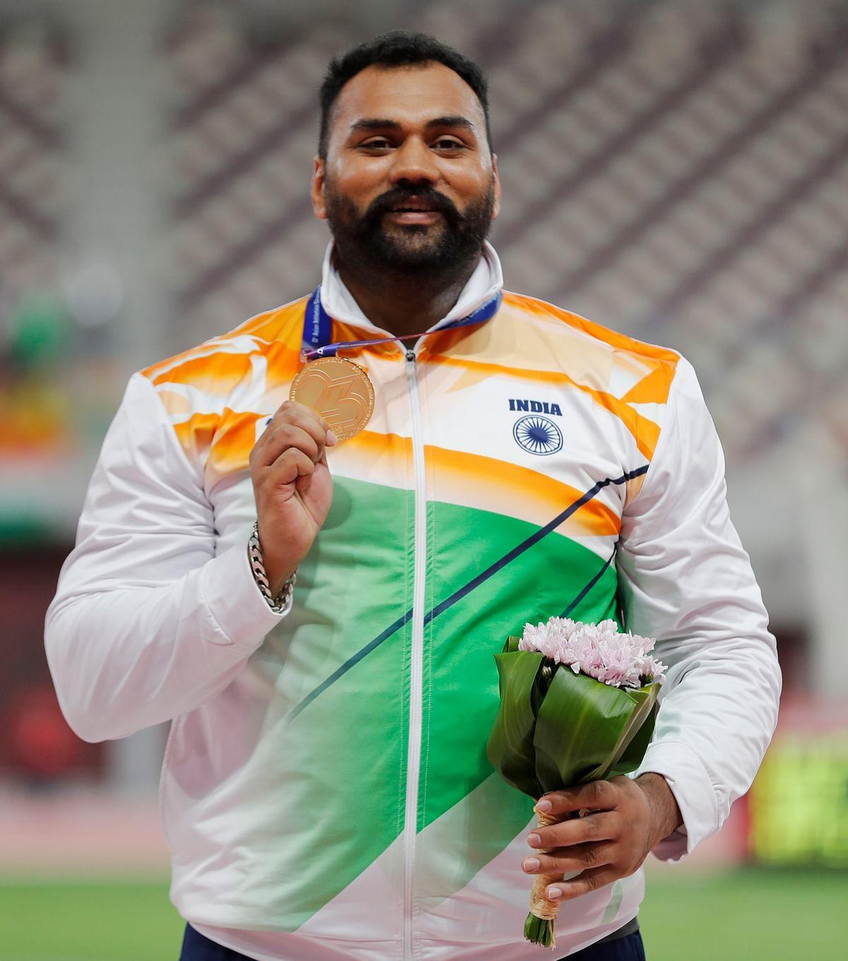 Tejinderpal Singh Toor celebrates after winning the gold medal.