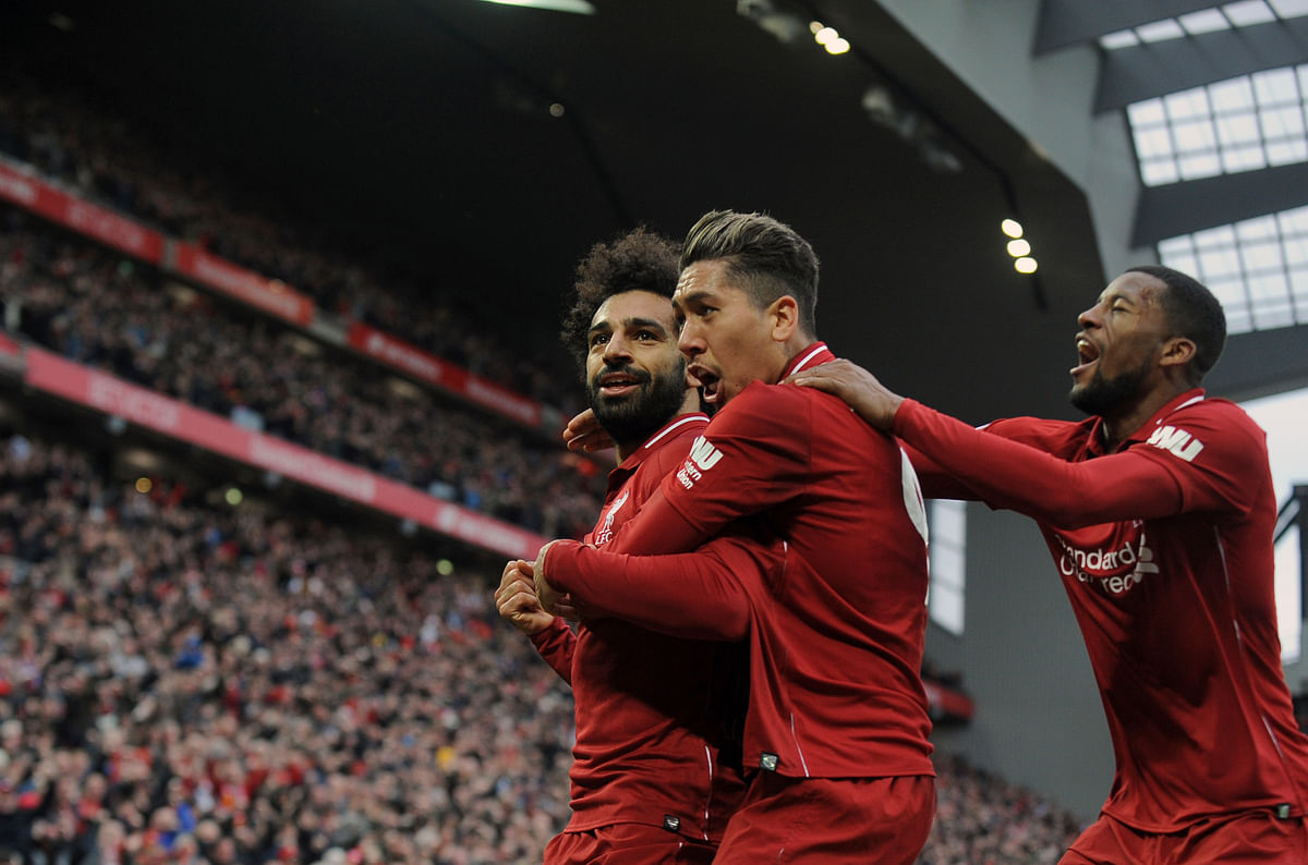 Liverpool's Mohamed Salah, left, Roberto Firmino, center, and Georginio Wijnaldum celebrate after Tottenham's Toby Alderweireld scores an own goal past his goalkeeper.